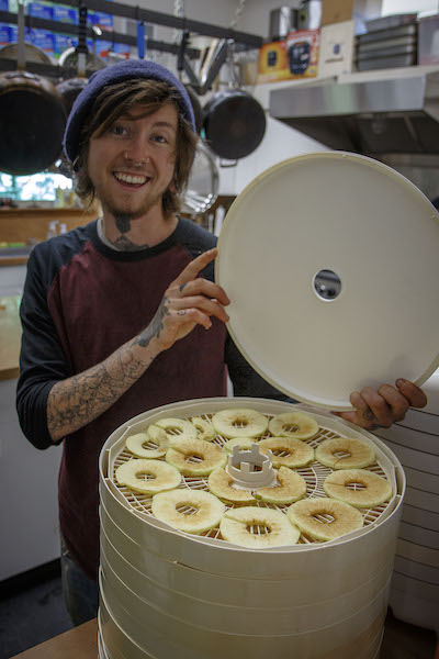 young man lifting lid off dehydrator
