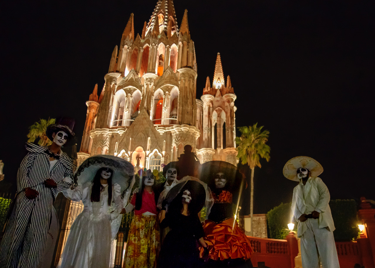 People dressed as fancy skeletons in front of a lit cathedral