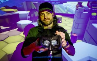 Bearded man holds headset with virtual reality screen in background