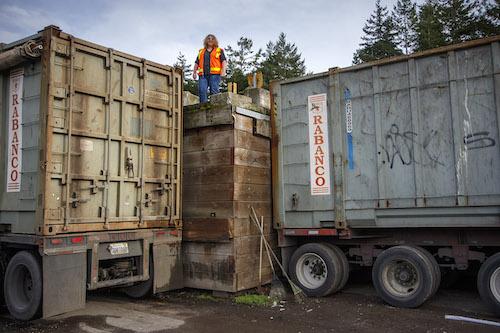 Woman stands between enormous trash bins