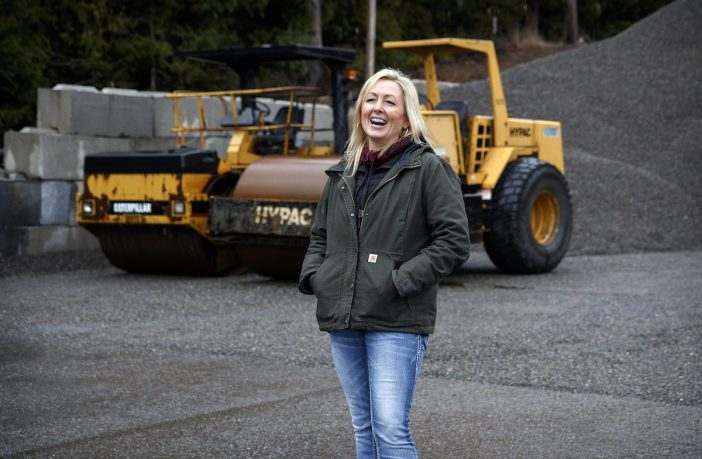 Blonde stands in front of road equipment.