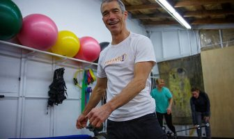 Smiling man with ladies lifting weights in the background