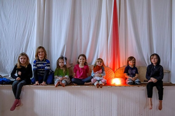 Children sit on a stage with white curtain and glowing pink light