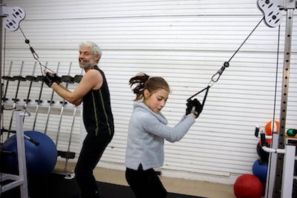 Silver-haired dad and daughter lift weights