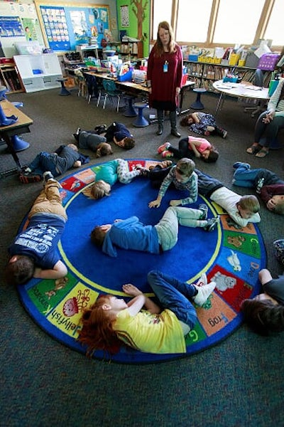 First graders curled up on a blue rug