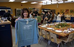 dark-haired woman holds large blue shirt while others cook behind her