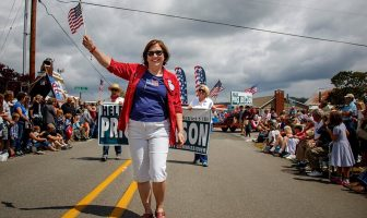 Island County Commissioner Helen Price Johnson in red jacket, blue shirt and white capris waves a flag while walking in a parade