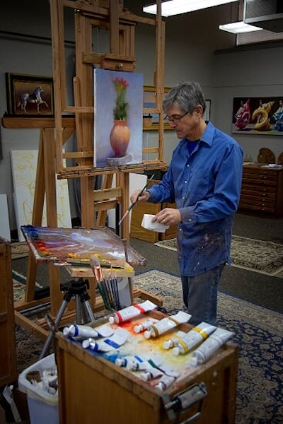 Man in blue shirt painting at an easel