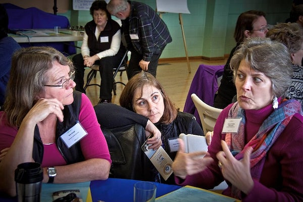 Woman listening to two women speak