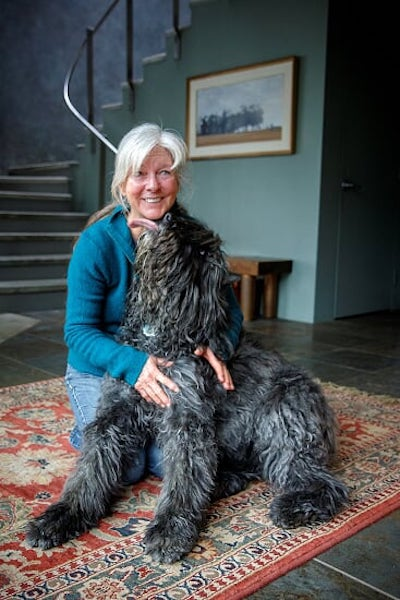 Woman with silver hair and big black shaggy dog licking her face
