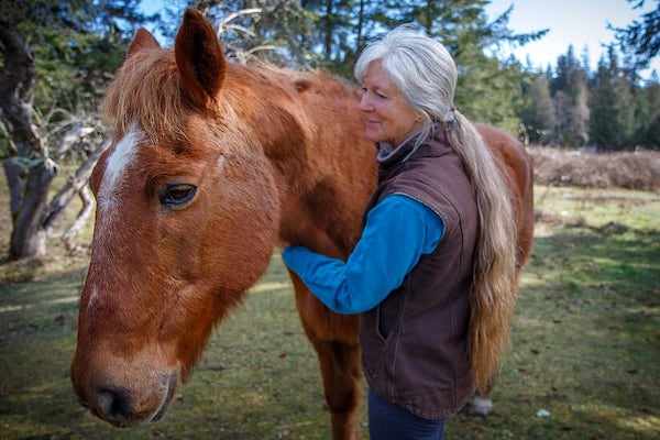 Woman with arms around a horse