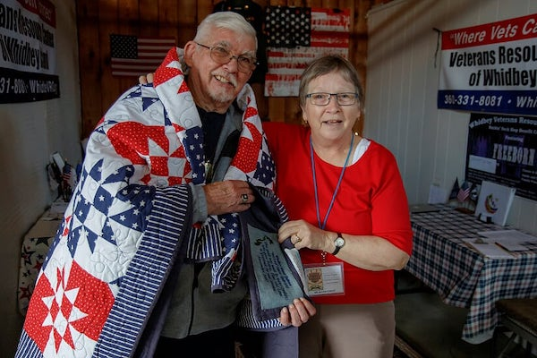 Silver-haired man in red, white and blue quilt.