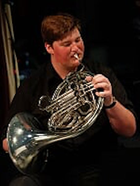 Young man playing French Horn