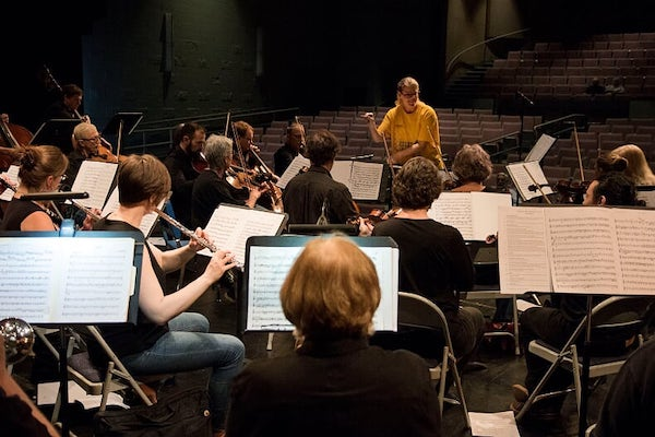 Woman in yellow t-shirt directing an orchestra