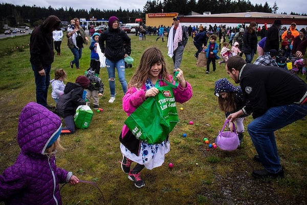 Girl in pink jacket with green bag gathering Easter eggs