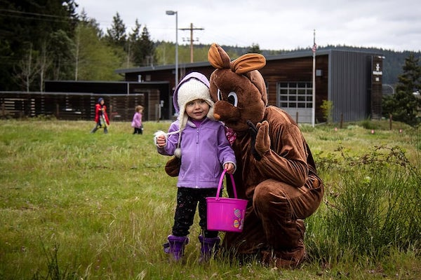 Brown-velour-costumed Easter Bunny hugs a little girl