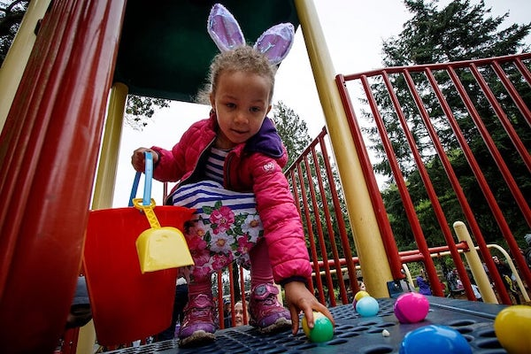 Girl in bunny ears picks up colored eggs.