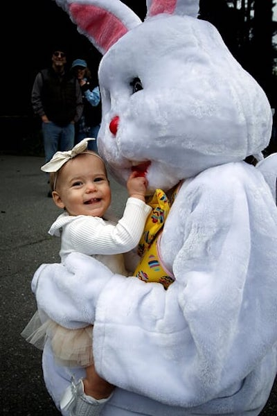 White-velour-costumed Easter Bunny hugs a toddler in a white bow